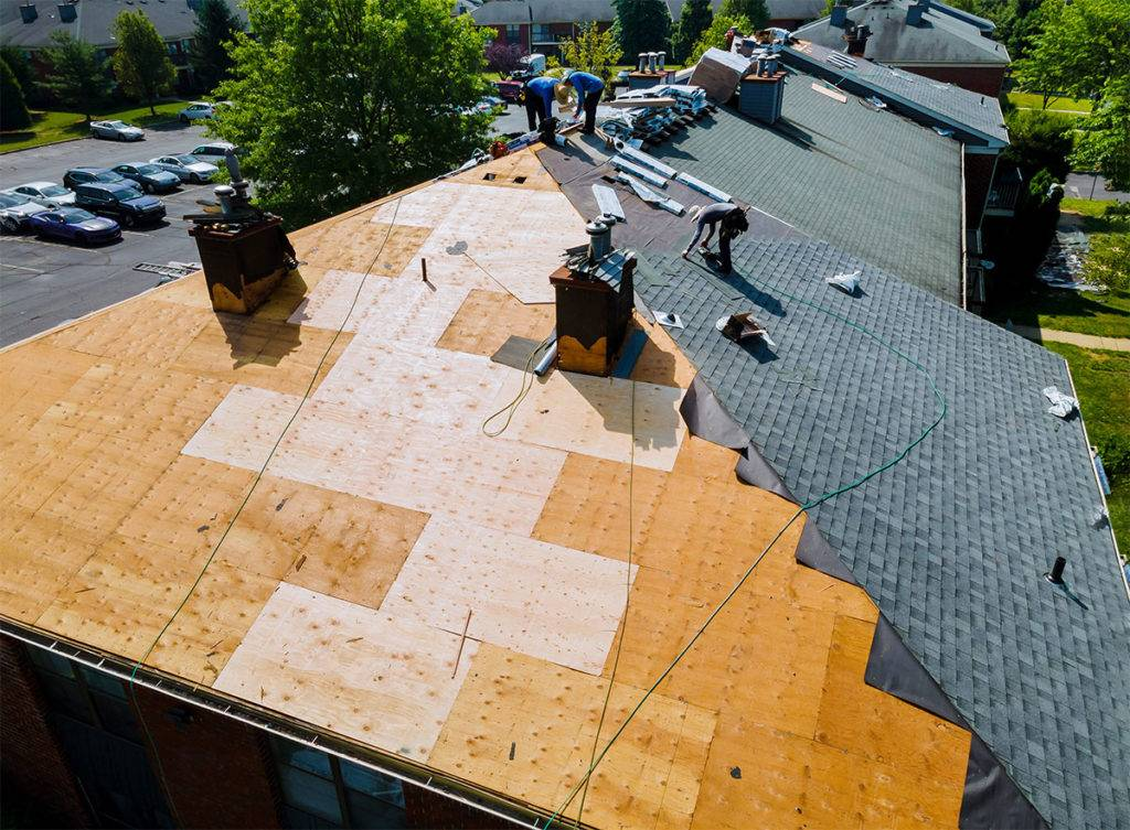 workers stapling shingles to roof